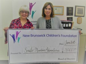 "Peggy Brittain, director presents to Sheila Lebrun, president Snider Mountain Adventures Inc. a grant cheque for $5,000 to help with costs of the ""New Horizons"" program for at risk youth. One weekend a month for 12-months youth attend the camp ""to give them the opportunity and confidence to see their future possibilities in a whole new way"" said Constable ---, RCMP and a founding volunteer. Sheila Lebrun agrees and said, ""We have some youth who don't want to leave when it's time because they are enjoying it so much."" Volunteers and staff make sure the time is well spent with healthy meals, games, crafts and riding some of the ranch horses. The New Brunswick Children's Foundation is a proud sponsor of this wonderful program to support our youth! Anyone interested in the program either to volunteer or donate can contact Snider Mountain Adventures at www.snidermountainranch.ca."